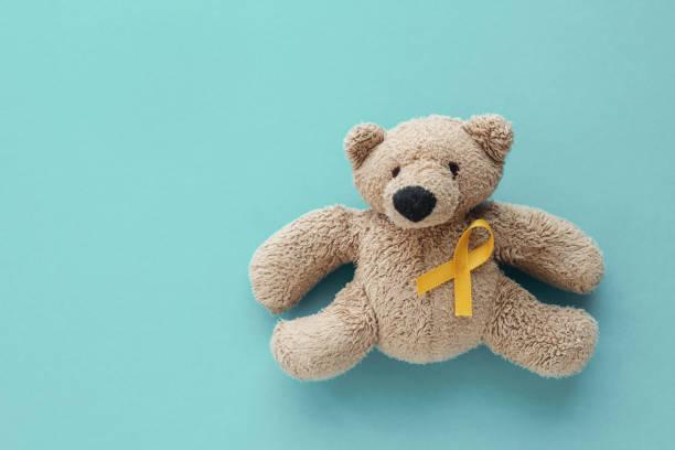 crianças urso marrom do brinquedo macio com fita amarela do ouro, consciência do cancro da infância - infância - fotografias e filmes do acervo
