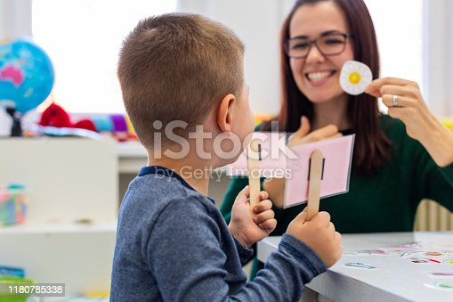 istock Children speech therapy concept. Preschooler practicing correct pronunciation with a female speech therapist. 1180785338
