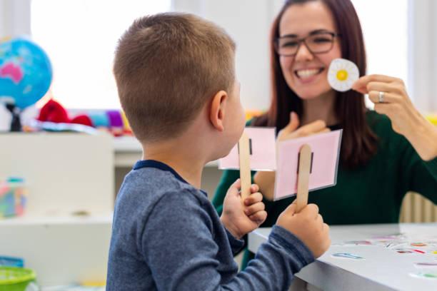 Kinder-Sprachtherapie-Konzept. Vorschulkind übt korrekte Aussprache mit einer weiblichen Logopädin. – Foto