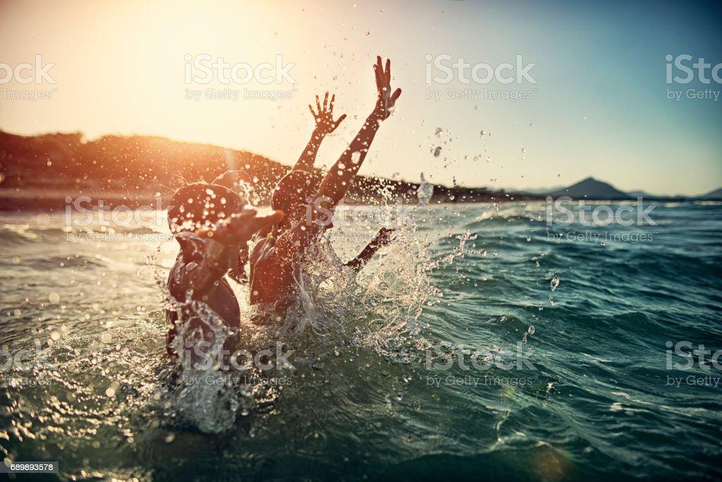 Children splashing in summer sea