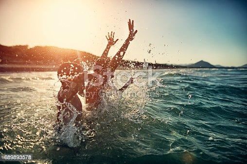 Children are having splashing fun in sea on summer sunset.  Children are aged 6 and 11.