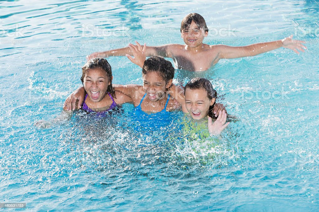 Children splashing in swimming pool. stock photo