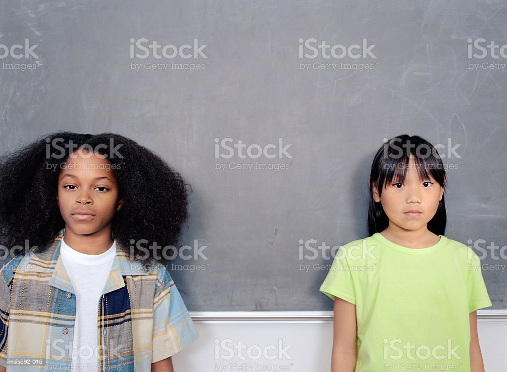 Children standing against blackboard royalty-free stock photo