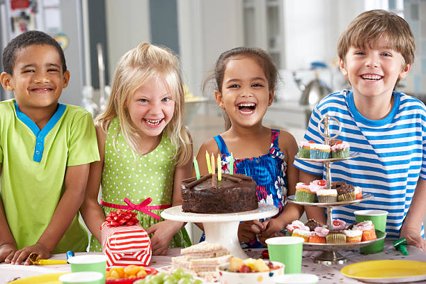 Children Standing By Table Laid With Birthday Party Foo stock photo