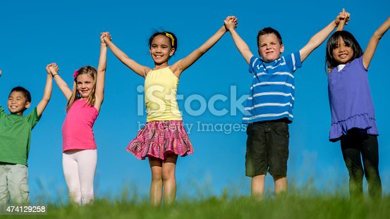 A multi-ethnic group of elementary age children standing together in a row, holding hands with their arms raised in the air, smiling and looking at the camera. Standing atop a grassy hill with the clear blue sky in the background.