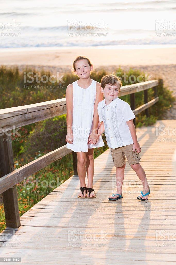 Crianças em pé na praia boardwalk - foto de acervo