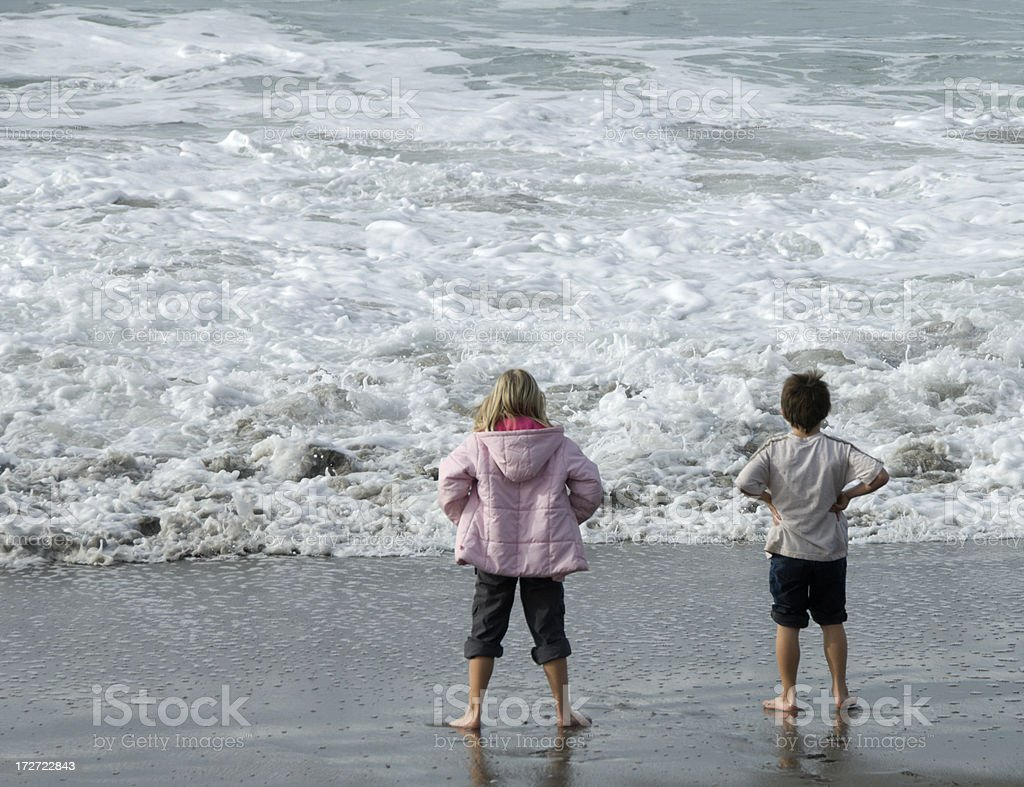 Children standing on the beach watching the surf royalty-free stock photo