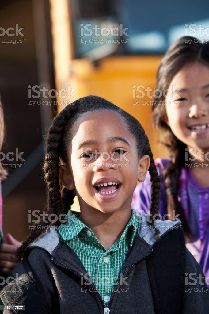 Children standing outside school bus stock photo