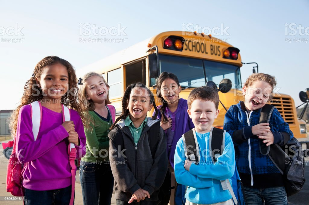 Children standing outside school bus stock photo