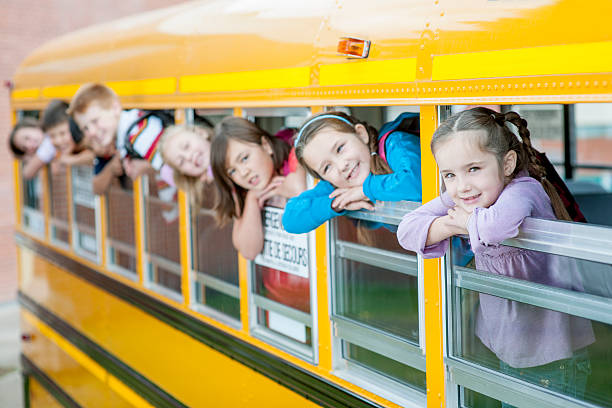 Children Sticking Their Heads Out of the School Bus A multi-ethnic group of elementary age children are in a school bus and have their heads out the window - they are smiling and looking at the camera. field trip stock pictures, royalty-free photos & images