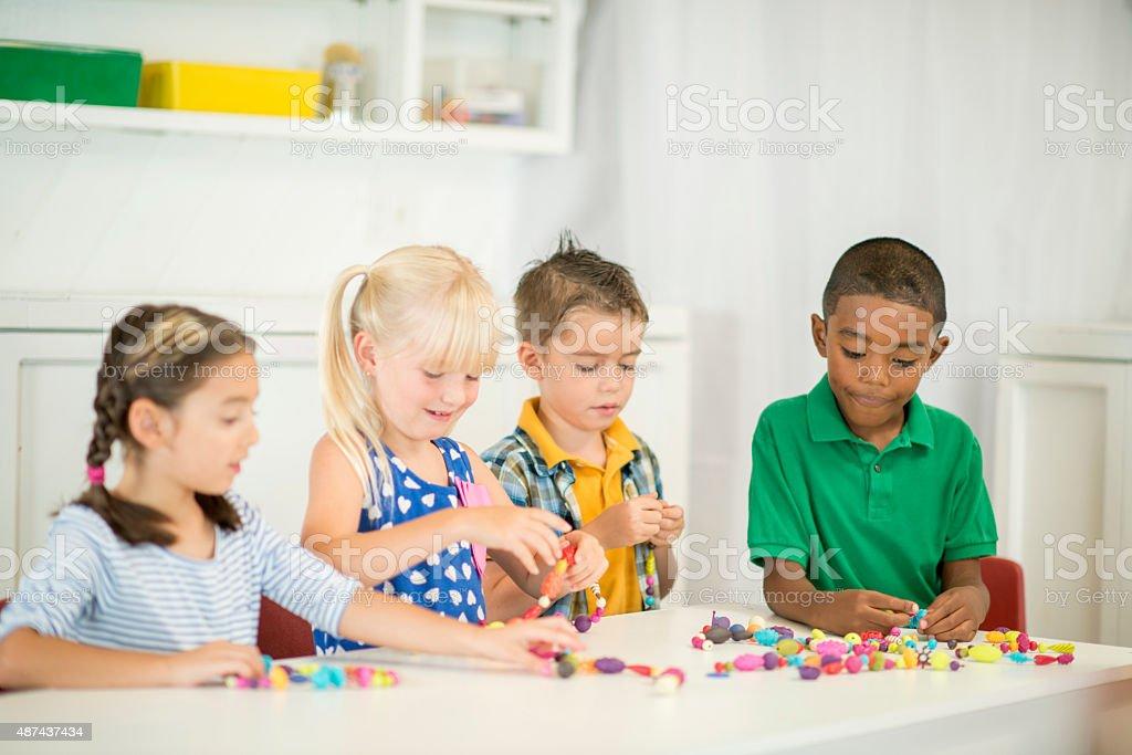 Children Stringing Beads stock photo