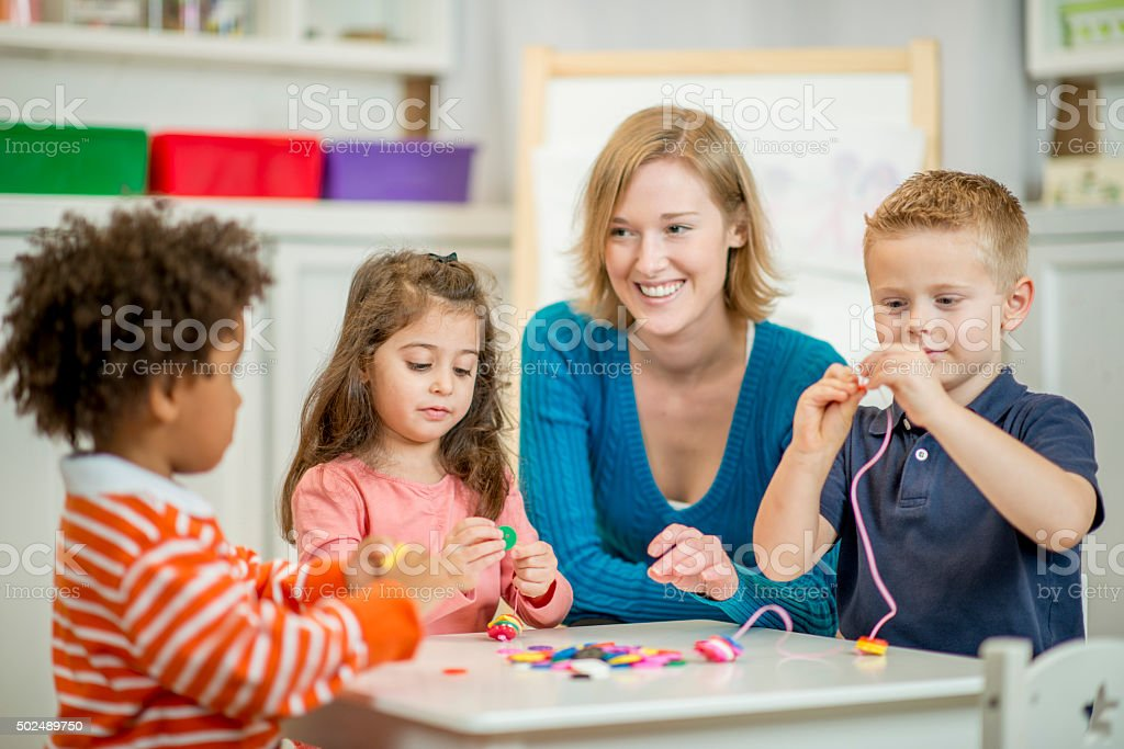 Children Stringing Beads Together stock photo