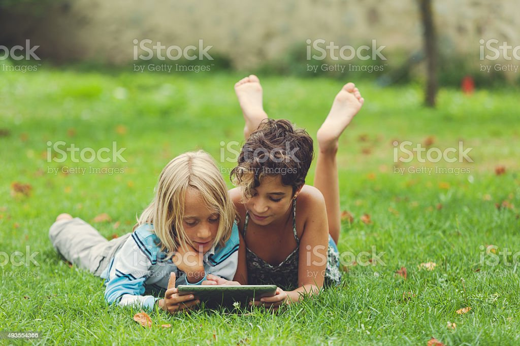 Children studying and playing on a tablet stock photo