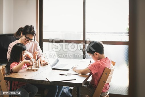 1053936526 istock photo Children studying at home and mother taking care of them 1226350274