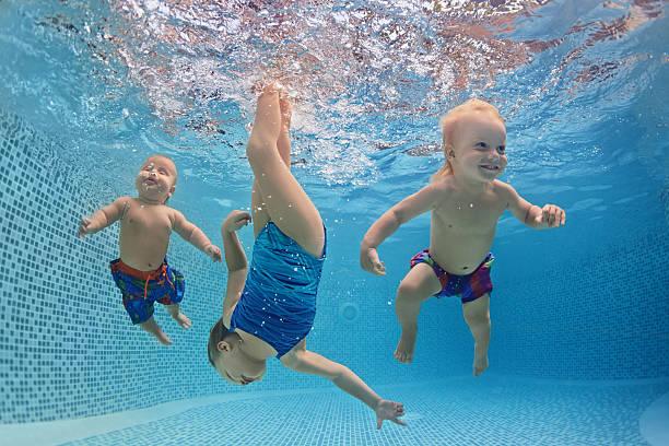 Children swim and dive underwater with fun in swimming pool stock photo