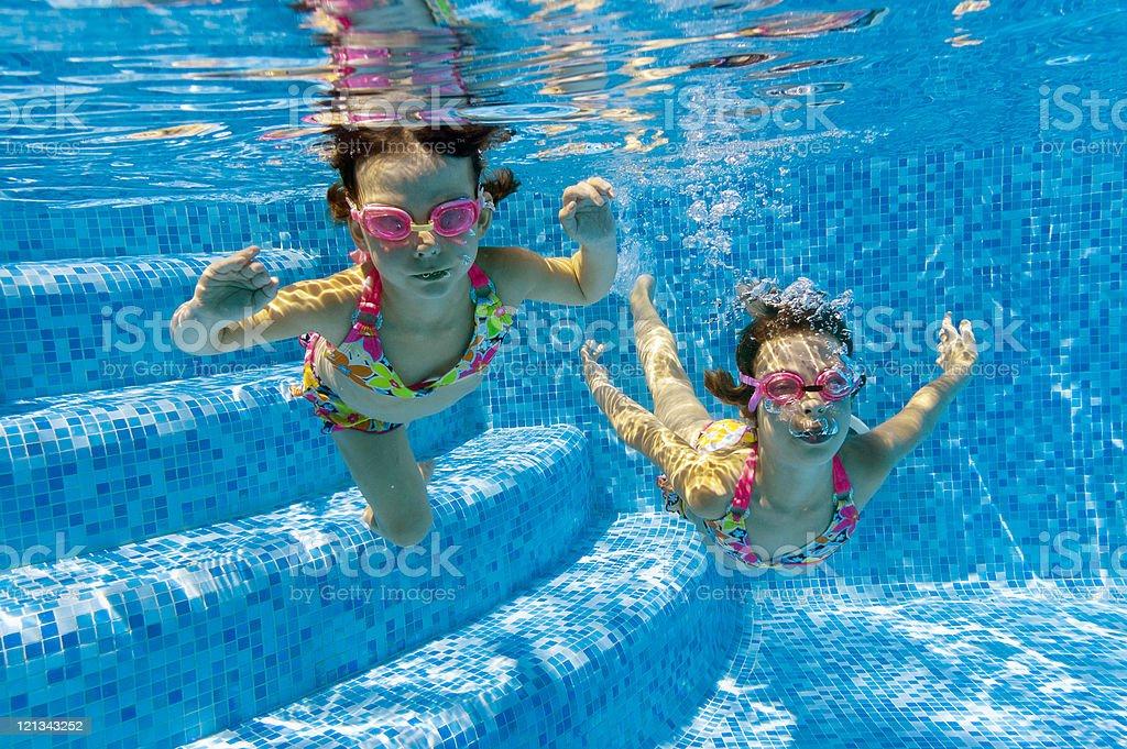 Children swimming underwater in pool royalty-free stock photo