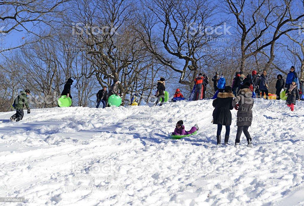 Children take advantage of freshly fallen snow to go sledding stock photo