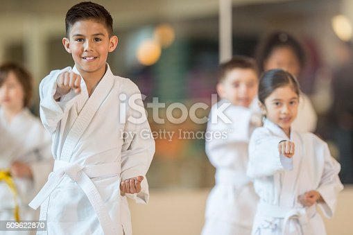 A multi-ethnic group of elementary age children are standing together in formation during their taekwando class. One boy is smiling while looking at the camera.
