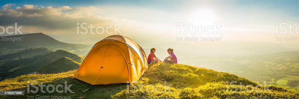 Children tent camping on idyllic summer sunset mountain top panorama stock photo