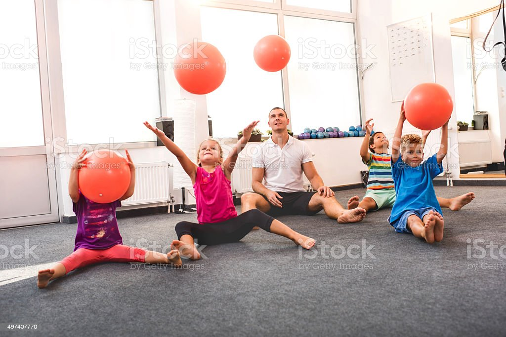 Children Throwing Balls On An Exercise Class With A Coach ...