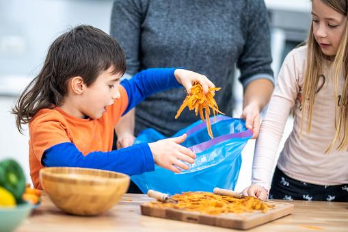Children throwing carrot peel in bag