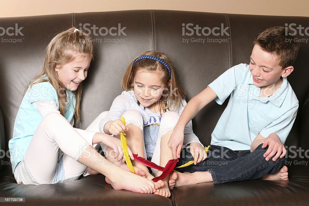 Children Tickling Feet With Feather stock photo | iStock