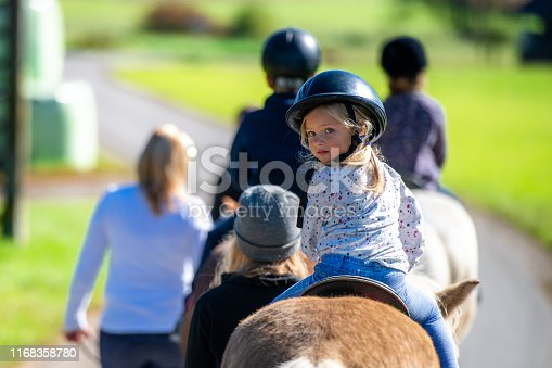 Children training horseback riding with the help of their parents on ranch.
