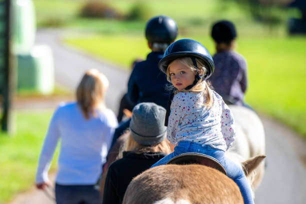 Children training horseback riding Children training horseback riding with the help of their parents on ranch. working animal stock pictures, royalty-free photos & images