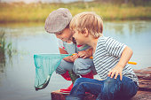Little boy and girl fishing from their raft