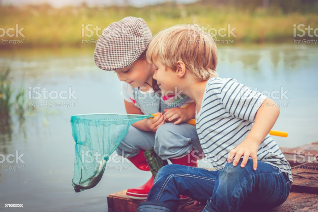 Children traveling on raft and fishing stock photo