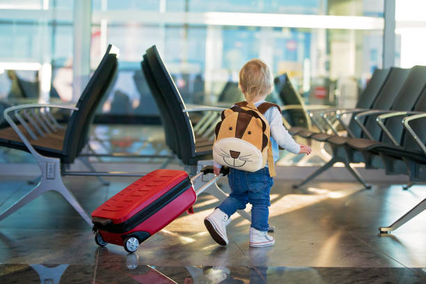 Los niños, viajando juntos, esperando en el aeropuerto para embarcar en el avión - foto de stock
