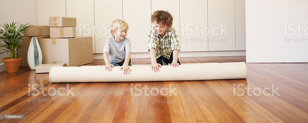 Children unrolling carpet in new house royalty-free stock photo