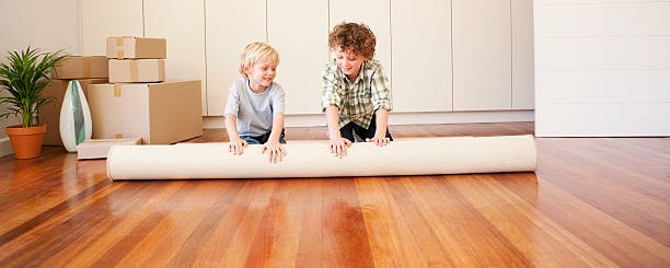 Children unrolling carpet in new house stock photo