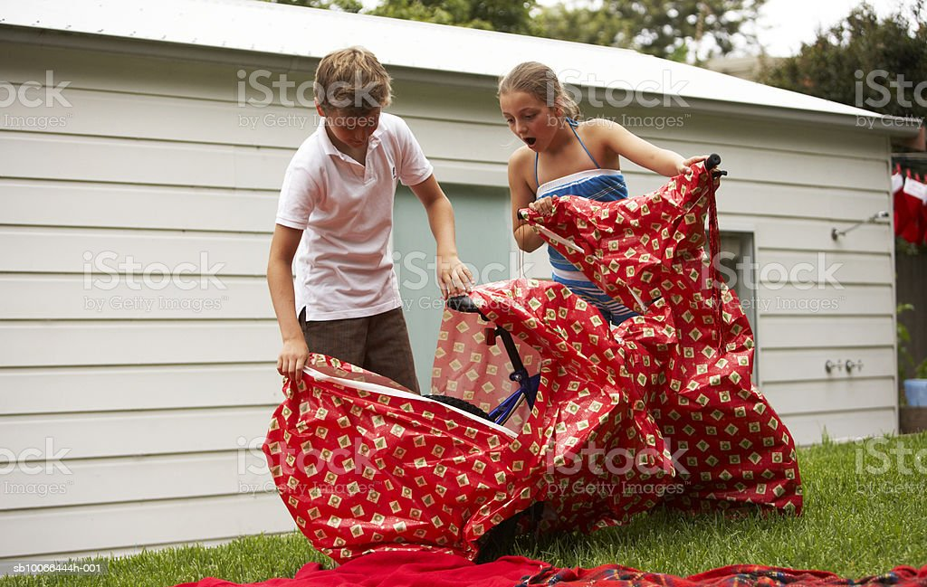 Children (9-12) unwrapping bicycle from wrapping paper in yard royalty-free stock photo
