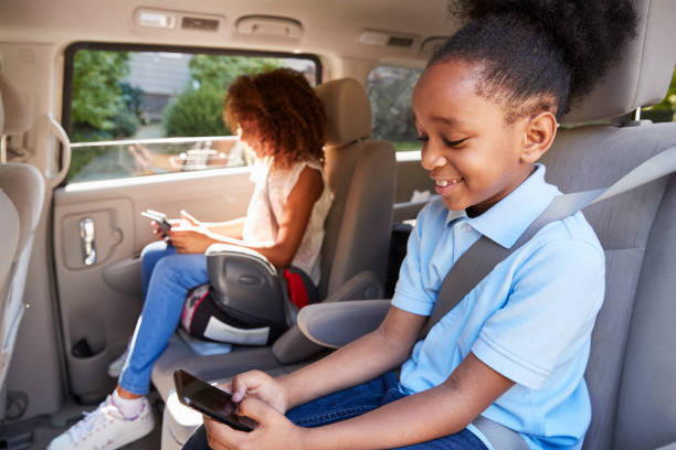 Children Using Digital Devices On Car Journey Children Using Digital Devices On Car Journey seat stock pictures, royalty-free photos & images