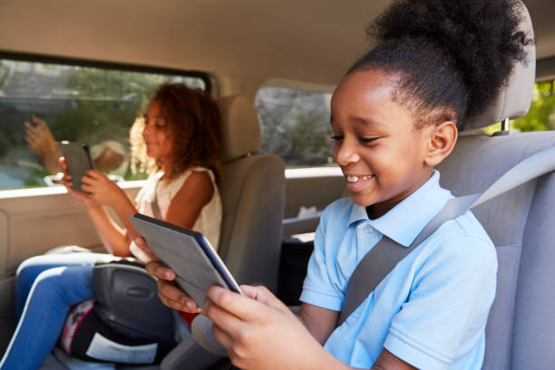Children Using Digital Devices On Car Journey stock photo