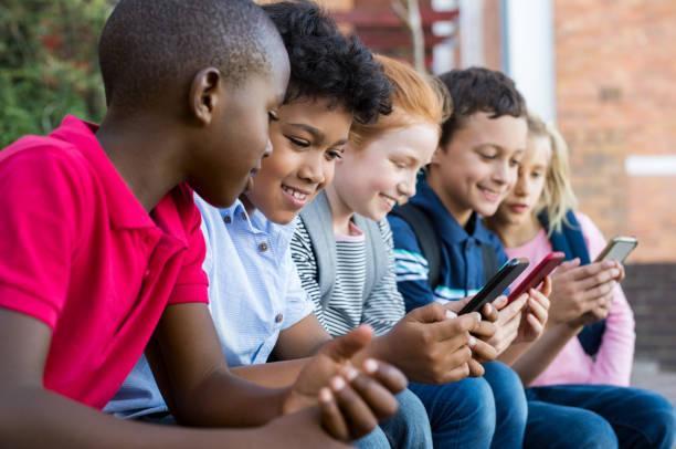 kinder mit smartphone - kind vor der pubertät stock-fotos und bilder