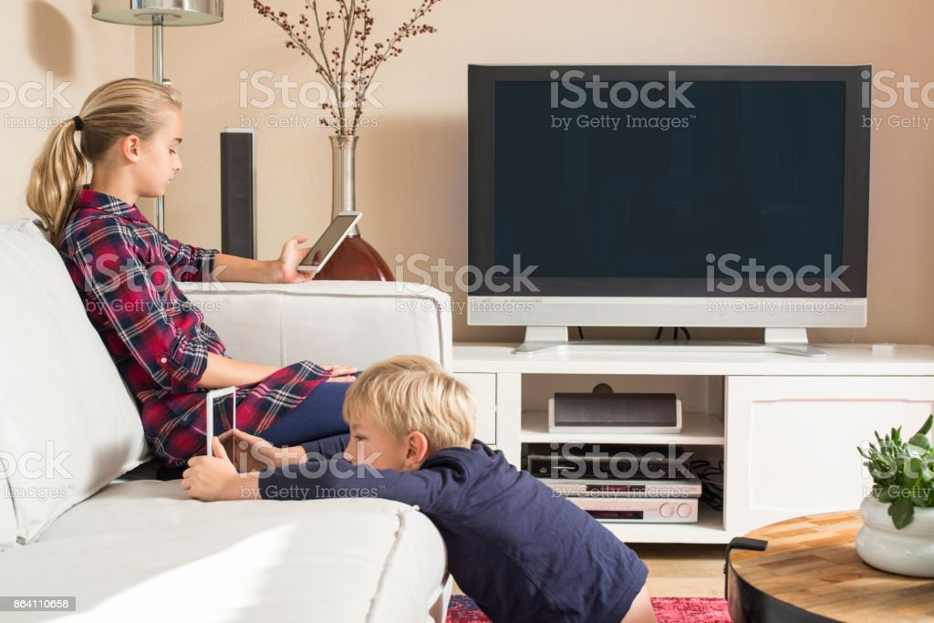 Children using tablet and smartphone in living room stock photo