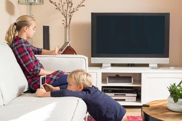 children using tablet and smartphone in living room - tv e familia e ecrã imagens e fotografias de stock
