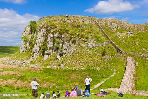 Cumbria, United Kingdom - June 23, 2015: Children Waiting for Rock Climbing at Hadrian Wall, Cumbria, United Kingdom. Steep rocky hill with green grass and blue sky with cloudsis are in background. HDR photorealistic image.
