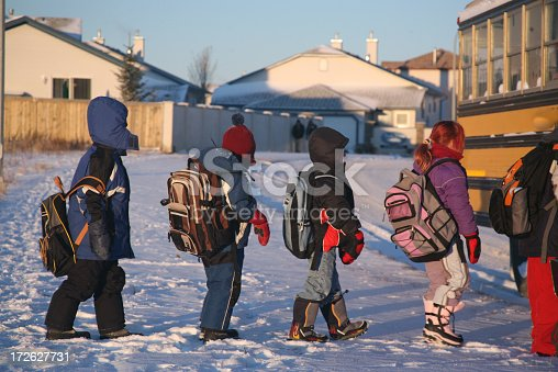 Cold children line up to board school bus in January. Children are bundled up in colorful winter coats, hats, boots, mittens, and carry backpacks. The ground is covered in snow. Residential houses, fence, etc. sjow up in the background. This picture was shot in Airdrie, Alberta, Canada.