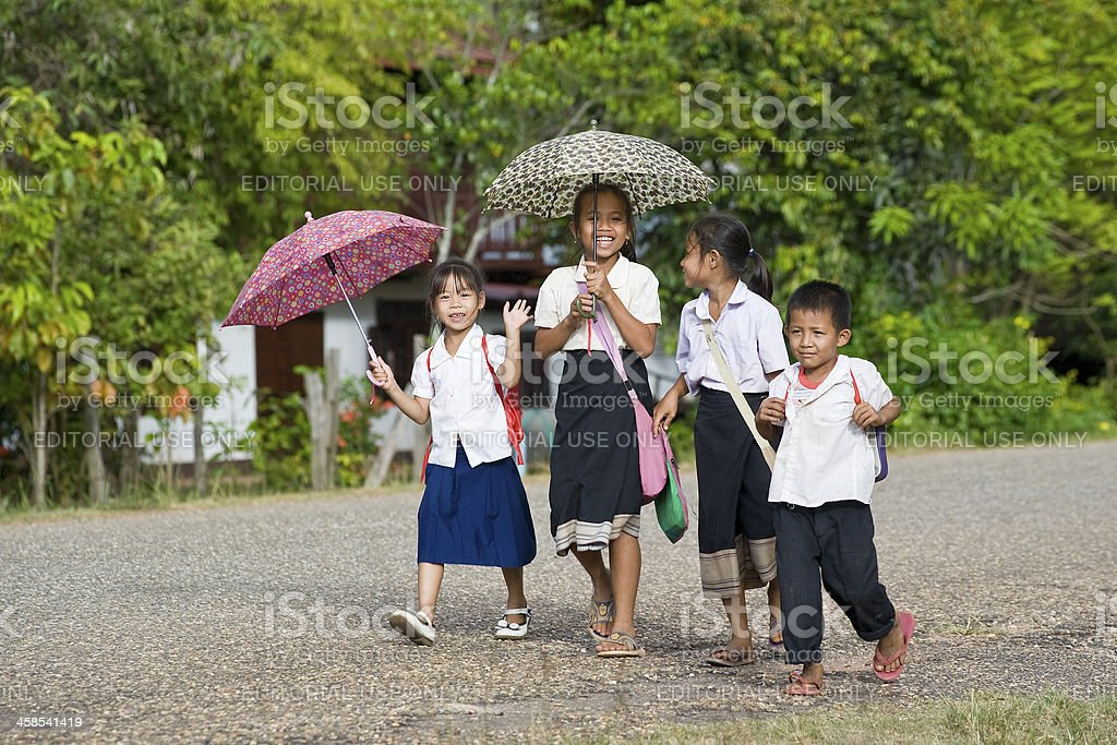 Children walking home from school with an umbrella, Laso stock photo