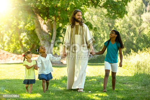 Stock photo of Jesus Christ walking with children on a bright sunny day.