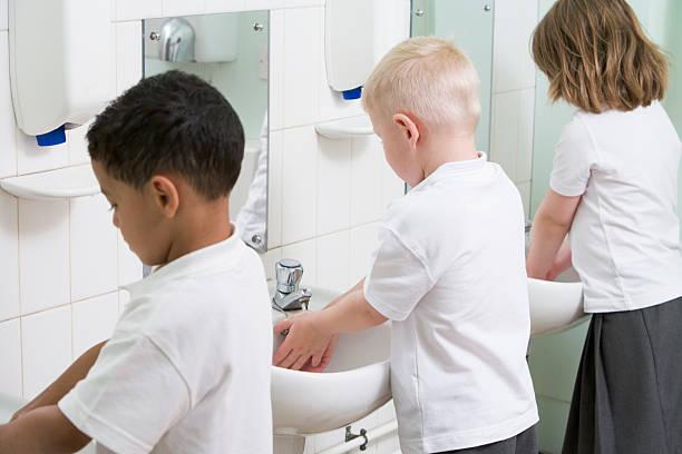 kinder waschen ihre hände in einer grundschule badezimmer - kinder wc stock-fotos und bilder