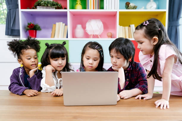 children watching film together on laptop stock photo