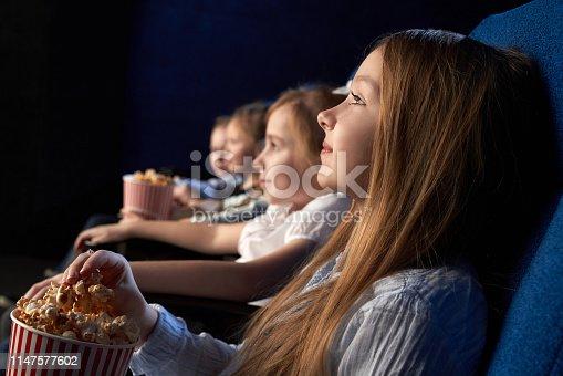 istock Children watching movie in cinema theatre. 1147577602