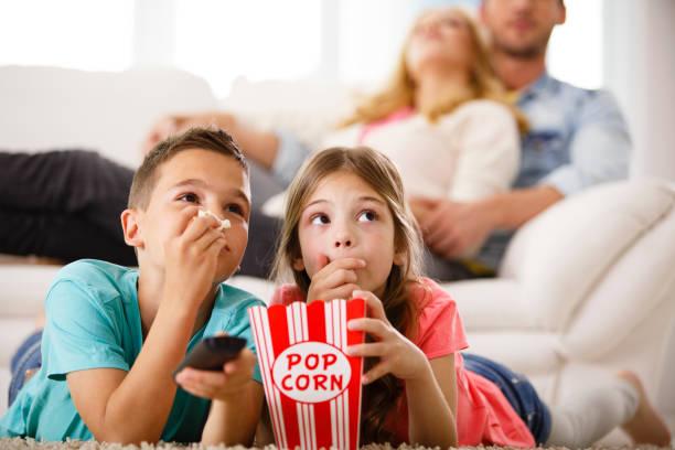 niños viendo televisión, comiendo palomitas de maíz - family watching tv fotografías e imágenes de stock