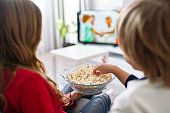 Kids is watching movie and eat popcorn