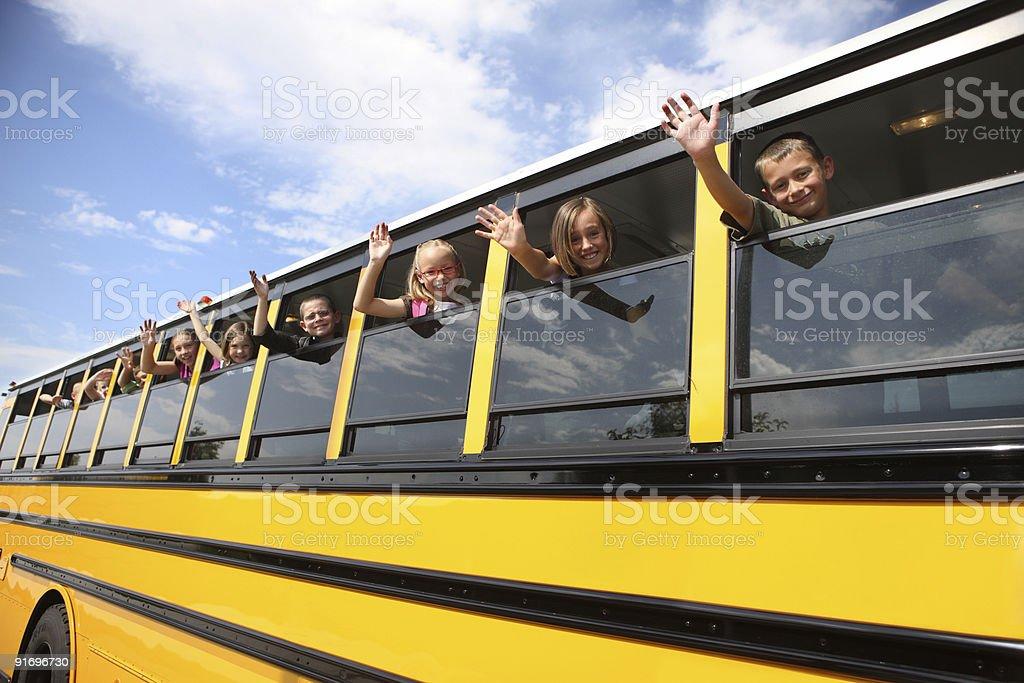 Children waving from school bus stock photo
