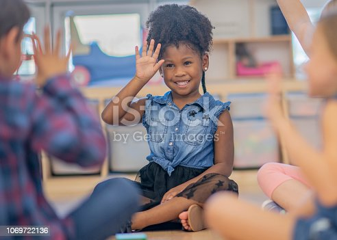 Children smile and wave as part of a song or game in their kindergarten classroom.